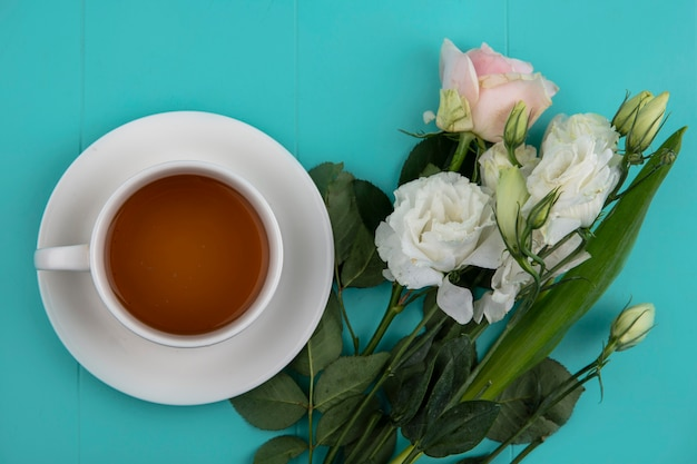 Draufsicht einer tasse tee mit frischen schönen blumen und blättern auf einem blauen hintergrund Kostenlose Fotos