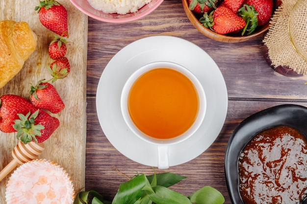 Draufsicht einer tasse tee mit frischer reifer erdbeermarmelade und hüttenkäse auf rustikalem holz Kostenlose Fotos