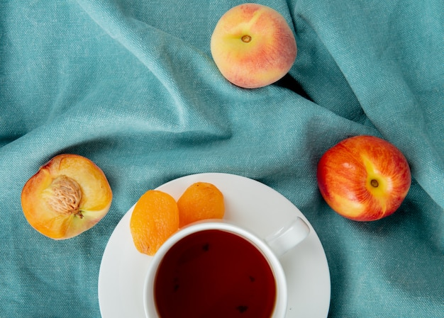 Draufsicht einer tasse tee mit getrockneten aprikosen und frischen reifen pfirsichen auf blau Kostenlose Fotos