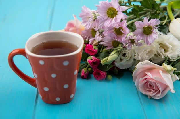 Draufsicht einer tasse tee mit wunderbaren frischen blumen lokalisiert auf einem blauen hölzernen hintergrund Kostenlose Fotos