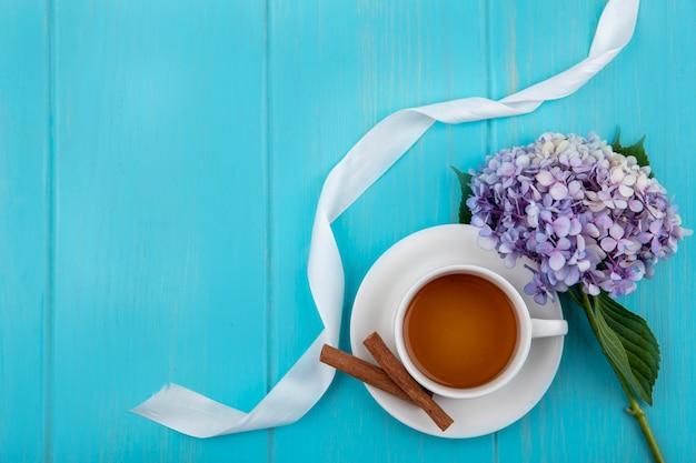 Draufsicht einer tasse tee mit zimtstangen mit schönen gardenzia-blumen auf einem blauen hölzernen hintergrund mit kopienraum Kostenlose Fotos
