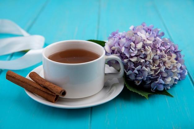 Draufsicht einer tasse tee mit zimtstangen mit schönen gardenzia-blumen auf einem blauen hölzernen hintergrund Kostenlose Fotos