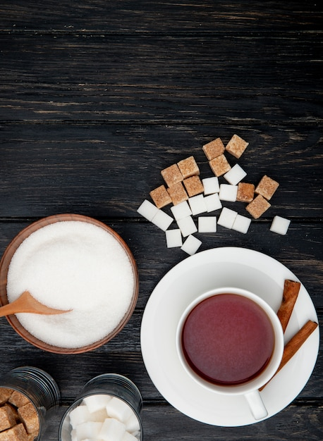 Draufsicht einer tasse tee mit zimtstangen und weißem kristallzucker in einer holzschale und klumpenzucker auf schwarzem hölzernem hintergrund Kostenlose Fotos