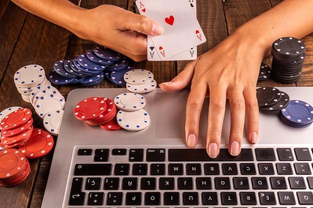 Draufsicht eines computers mit pokerchips und karten für das wetten oder das spielen. Premium Fotos