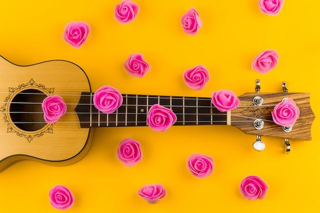 Draufsicht eines gitarren- und rosenblumenmusters auf vibrierendem gelb Premium Fotos