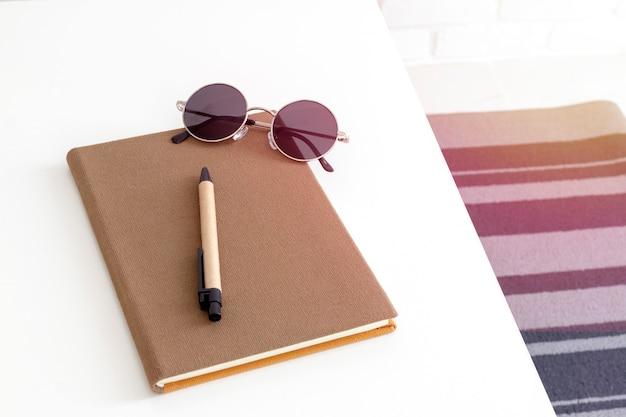 Draufsicht eines notizbuches, des stiftes und der sonnenbrille auf weißer tabelle. Premium Fotos