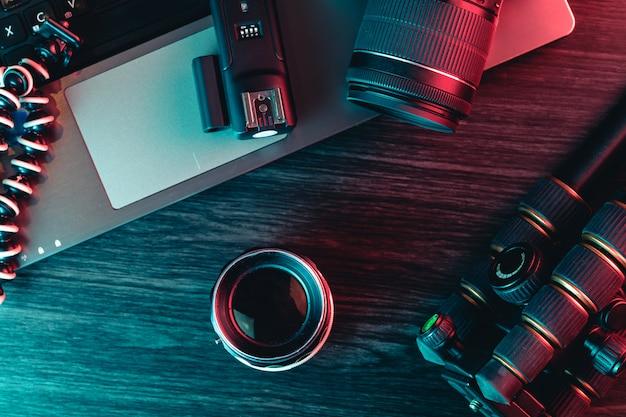 Draufsicht eines schreibtisches, der mit laptoptastatur, moderner kamera, linse, stativ und einem stift arbeitet Premium Fotos