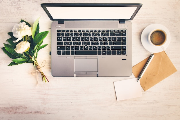 Draufsicht eines schreibtisches mit computer, umschlag, unbelegter anmerkung und einem bündel pfingstrosenblumen. Premium Fotos