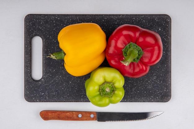 Draufsicht farbige paprika gelbgrün und rot auf einem schneidebrett mit einem messer auf weißem hintergrund Kostenlose Fotos
