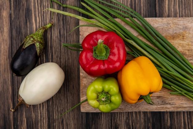 Draufsicht farbige paprika mit frühlingszwiebeln auf einem schneidebrett mit weißen und schwarzen auberginen auf hölzernem hintergrund Kostenlose Fotos