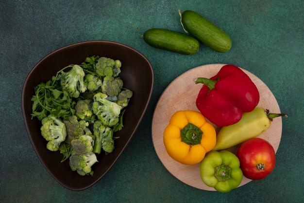 Draufsicht farbige paprika mit tomate auf einem ständer und gurken mit brokkoli auf einem grünen hintergrund Kostenlose Fotos