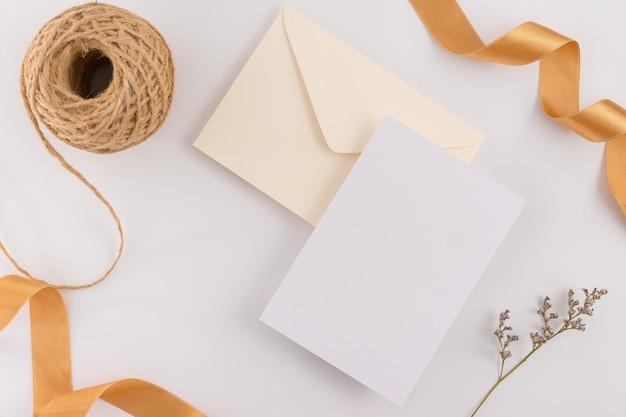 Draufsicht, flache lage, hochzeitseinladungskarte, umschläge, kartenpapiere auf weißem hintergrund. Premium Fotos