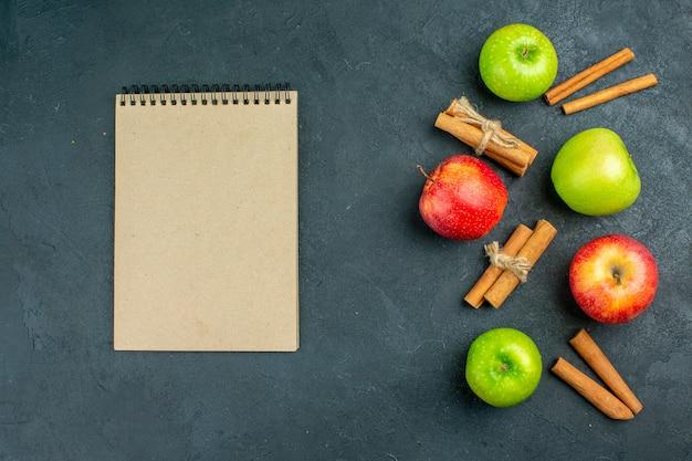 Draufsicht frische äpfel zimtstangen notizbuch auf dunkler oberfläche Kostenlose Fotos