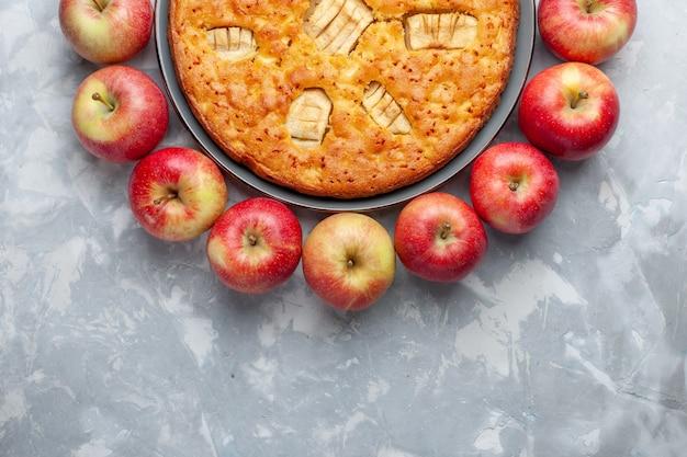 Draufsicht frische rote äpfel bilden kreis mit apfelkuchen auf dem hellen schreibtischfrucht frisches weiches reifes vitamin Kostenlose Fotos