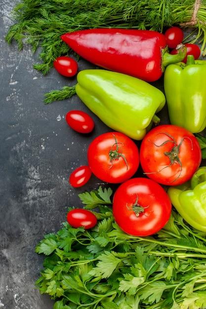 Draufsicht frisches gemüse rote und grüne paprika kirschtomaten dill petersilie tomaten auf dunkler oberfläche Kostenlose Fotos