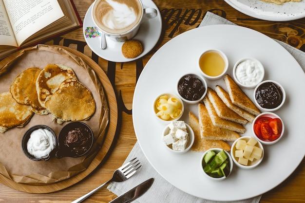 Draufsicht frühstücksset pfannkuchen mit schokoladenaufstrich und sauerrahm toast mit marmelade schokoladenaufstrich honig käse gurke tomatenbutter und tasse kaffee auf dem tisch Kostenlose Fotos