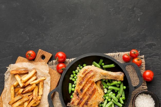Draufsicht gebackene hähnchen- und erbsenschoten in der pfanne mit kartoffeln und tomaten mit kopierraum Kostenlose Fotos