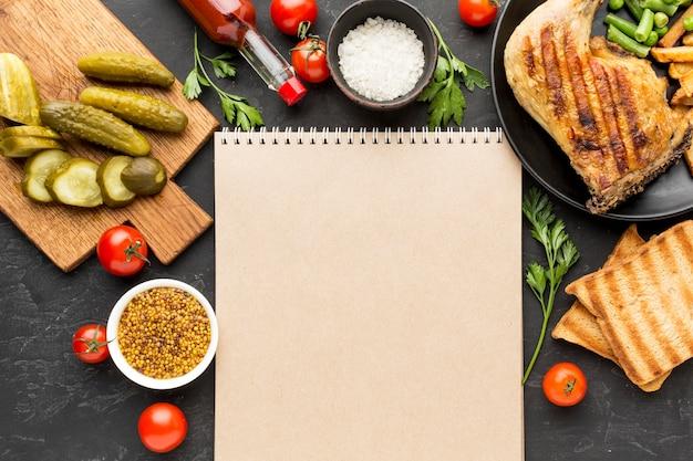 Draufsicht gebackenes huhn und kartoffeln auf teller mit gurken und leerem notizblock Kostenlose Fotos