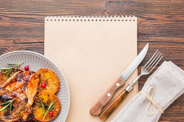 Draufsicht gebackenes huhn und orangenscheiben auf teller mit besteck und leerem notizbuch Kostenlose Fotos