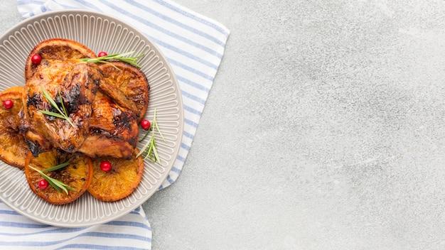 Draufsicht gebackenes huhn und orangenscheiben auf teller mit küchentuch und kopierraum Kostenlose Fotos
