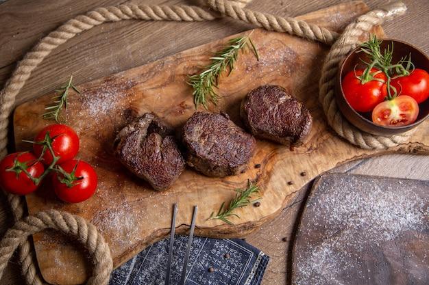 Draufsicht gebratenes leckeres fleisch mit frischen roten tomaten und grüns auf dem hölzernen schreibtischmahlzeitnahrungsmittelessen-fleischfoto Kostenlose Fotos