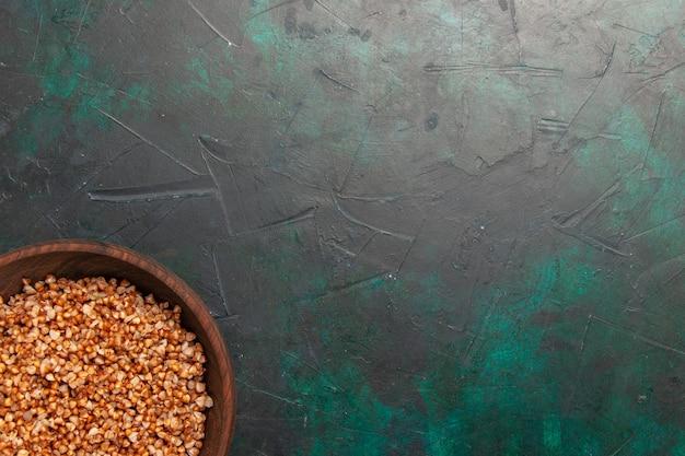 Draufsicht gekochte buchweizen-schmackhafte mahlzeit innerhalb der braunen platte auf der dunkelgrünen oberfläche Kostenlose Fotos