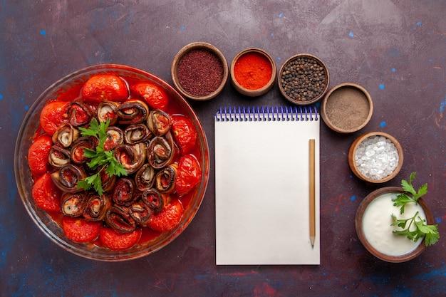 Draufsicht gekochte gemüsemahlzeit köstliche tomaten und auberginen mit gewürzen auf dem dunklen schreibtisch Kostenlose Fotos