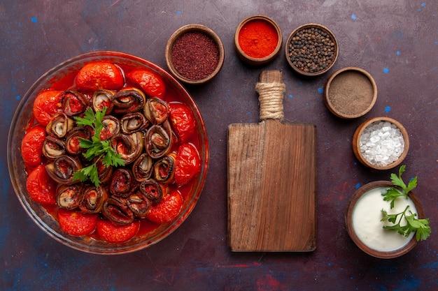 Draufsicht gekochte gemüsemahlzeit köstliche tomaten und auberginen mit gewürzen auf der dunklen oberfläche Kostenlose Fotos