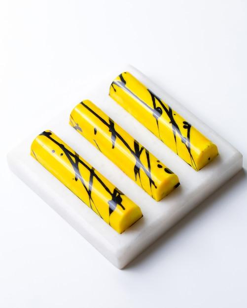 Draufsicht gelb im schwarzen fleck praline auf weißem stand Kostenlose Fotos