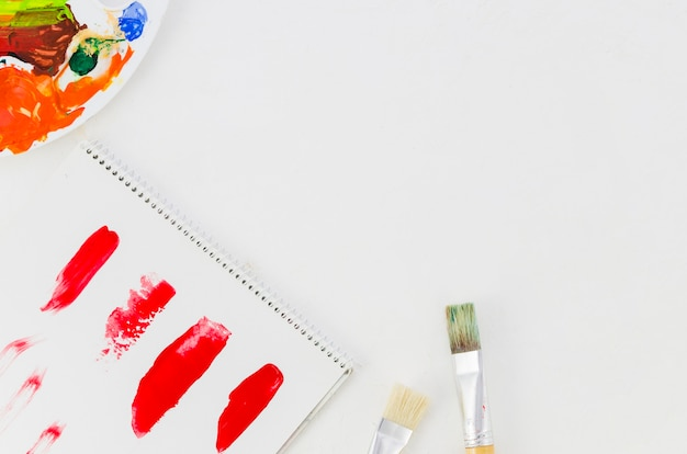 Draufsicht gemaltes papier, pinsel und palette Kostenlose Fotos