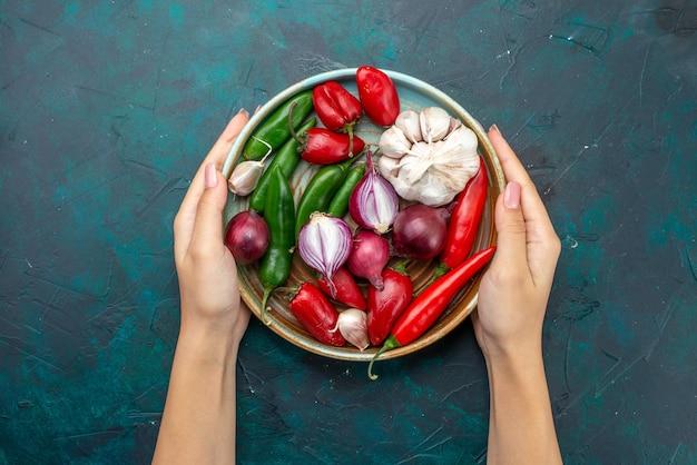 Draufsicht gemüsekomposition zwiebeln knoblauch paprika von frau auf dem dunklen tisch gemüsesalat lebensmittel mahlzeit farbe berührt Kostenlose Fotos
