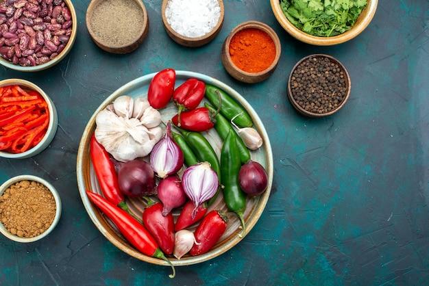 Draufsicht gemüsezusammensetzung zwiebeln knoblauch paprika gewürze auf dem dunkelblauen hintergrund lebensmittel mahlzeit zutat produktfarbe Kostenlose Fotos