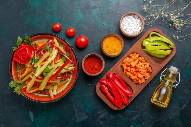 Draufsicht geschnittener paprika verschiedenfarbiger gemüsesalat mit zutaten und öl auf dunkelblauem hintergrund Kostenlose Fotos