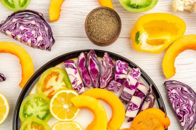 Draufsicht geschnittenes gemüse und obst kürbis persimone rotkohl zitronengrüne tomaten gelbe paprika auf schwarzer platte schwarzer pfeffer in schüssel auf tisch Kostenlose Fotos