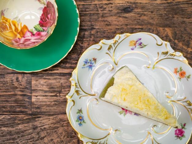 Draufsicht, gesüßter käsekuchen des grünen tees, der mit weißer schokolade übersteigt, setzte an eine weiße platte. Premium Fotos