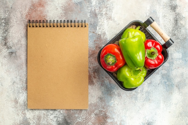 Draufsicht grüne und rote paprika in schüssel ein notizbuch auf nackter oberfläche Kostenlose Fotos