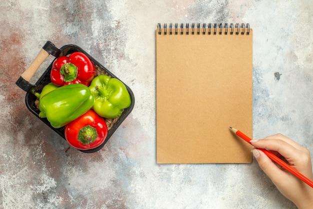 Draufsicht grüne und rote paprikaschoten in der schüssel ein roter notizbuchstift in weiblicher hand auf nackter oberfläche Kostenlose Fotos