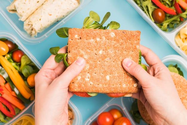 Draufsicht hände, die crackersandwich halten Kostenlose Fotos