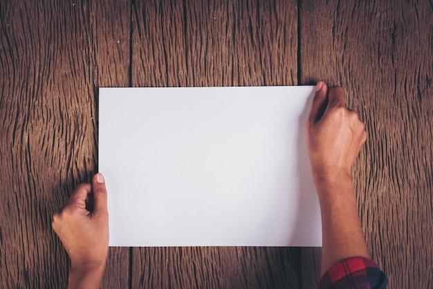 Draufsicht hand mit leerem weißbuch Kostenlose Fotos