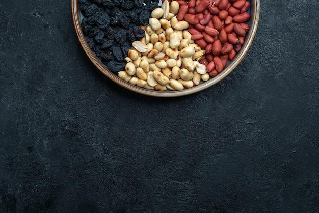 Draufsicht haselnüsse und rosinen und andere nüsse auf dunkelgrauem hintergrundnuss-snack-trockenobst Kostenlose Fotos