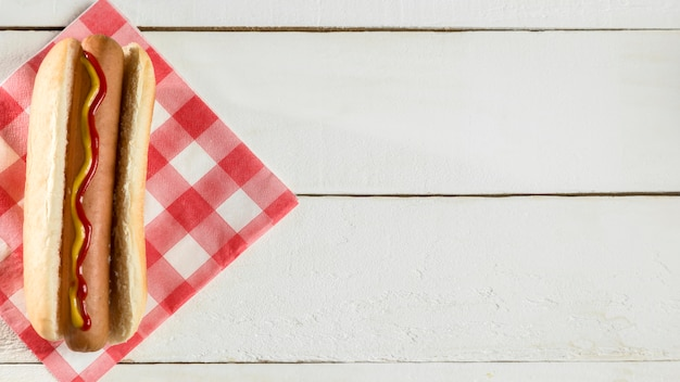 Draufsicht hot dog mit serviette auf hölzernem hintergrund Kostenlose Fotos