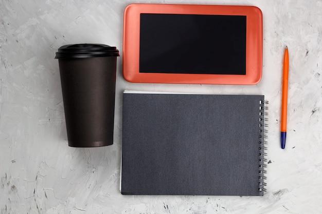 Draufsicht kaffee zum mitnehmen tasse, tablette und notizblock Premium Fotos