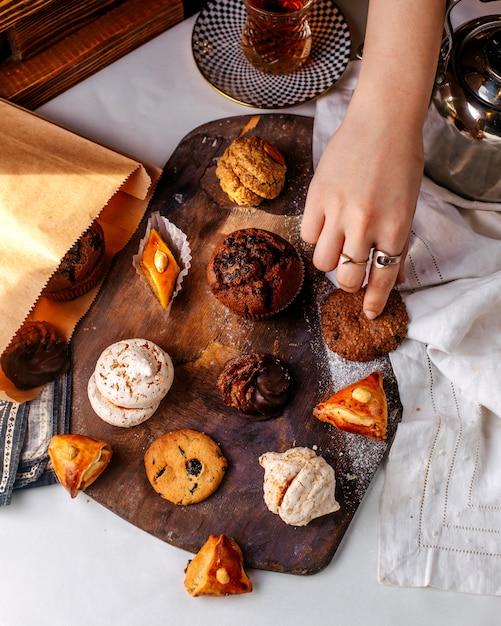 Draufsicht kekse und kuchen auf dem braunen holzschreibtisch auf der hellen oberfläche Kostenlose Fotos