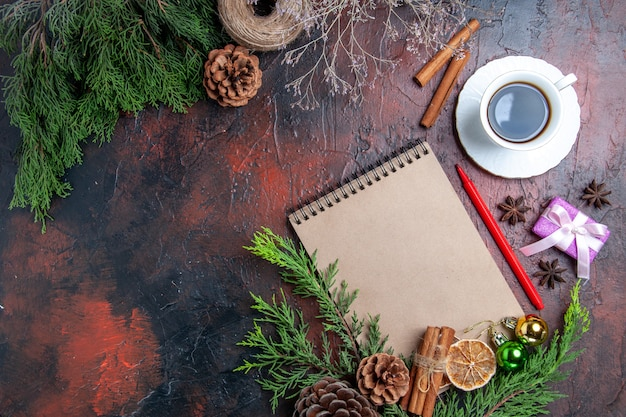 Draufsicht kiefernzweige und tannenzapfen ein notizbuch roter stift getrocknete zitronenscheiben strohfaden tasse tee sternanis auf dunkelroter oberfläche mit freiem platz Kostenlose Fotos
