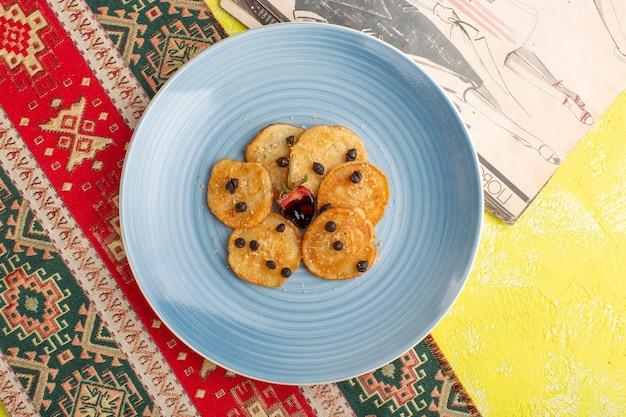Draufsicht kleine keksgebäck innerhalb der blauen platte auf gelbem tisch, backen sie süßes teegebäck Kostenlose Fotos