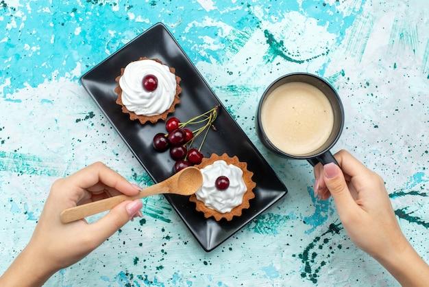 Draufsicht kleine köstliche kuchen mit sahne und fruchtmilch auf dem blaulicht-tischkuchen süße sahne backen frucht Kostenlose Fotos