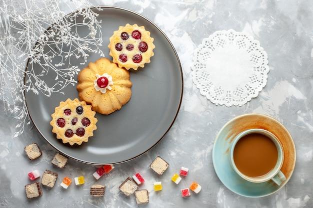 Draufsicht kleine kuchen innerhalb der grauen platte mit milchkaffee auf dem hellen schreibtischkuchenkekskaffeezuckersüß Kostenlose Fotos