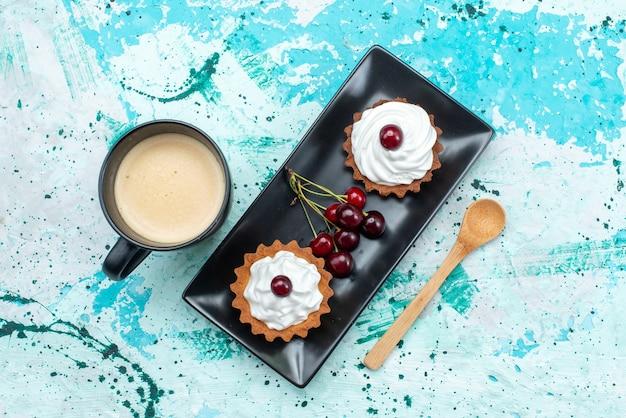 Draufsicht kleine kuchen mit zuckerpulverfruchtcreme zusammen mit kirschenmilch auf hellem hintergrundkuchencremefrucht süßer tee Kostenlose Fotos