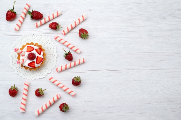 Draufsicht kleine leckere kuchen mit sahne und geschnittenen erdbeersüßigkeiten auf dem weißen hintergrundkuchenbeeren-süßen auflauf Kostenlose Fotos