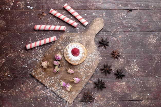 Draufsicht kleiner cremiger kuchen mit himbeere zusammen mit rosa stockbonbons auf dem braunen hölzernen hintergrundbonbon süßer zucker backen kuchen Kostenlose Fotos